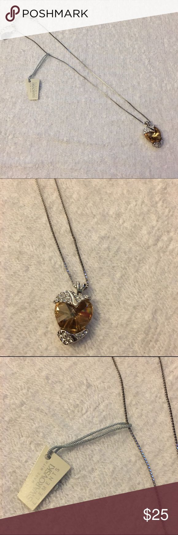Eric Andrew Collection-Swarovski elements necklace Eric Andrews Collection necklace with adjustable clasp. Heart shaped amber Swarovski center crystal with white Swarovski crystal accents, all on a silver chain. Eric Andrews Collection Jewelry Necklaces