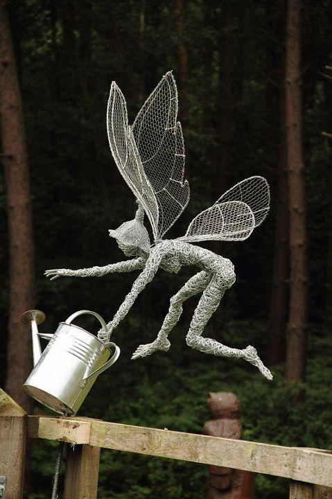 wire and chicken wire fairy this piece has an engraved stone for a heart, and is sized to be  garden ornament.