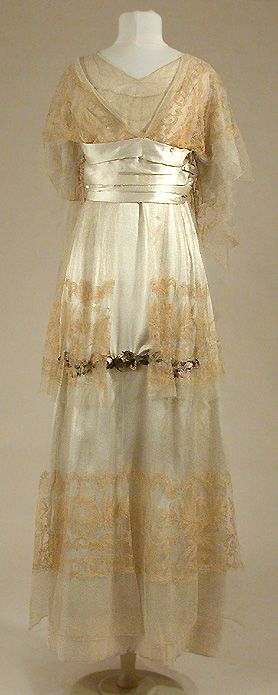 Afternoon gown, House of Paquin, 1912.  Silk underskirt overlaid with three tiers of Alencon lace, appliquéed with garland of silk rosebuds on the front of the skirt. Empire waist with pleated satin cummerbund sash with coral trim on the back. Lace bodice extends to cape at the back   JV
