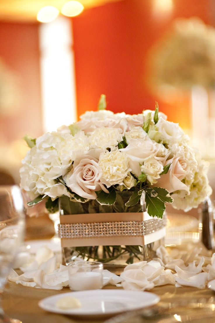 Low centerpiece vase wrapped with Raw Silk ribbon and rhinestone trim.  Filled with white hydrangea, ivory, champange and blush roses, ivory spray roses, ivory carnations, and white lisianthus.  Photo courtesy of Catherine McKinley Photography.