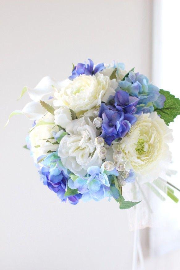 『ブルーハンドメイド2017』♡サムシングブルーのブーケ♡ ブートニア付き。ブルーのブーケは花嫁さんを清楚で上品に見せてくれる効果があり幸せな結婚式にとてもオススメ♪濃淡のブルーのあじさいを使って爽やかな雰囲気に仕上げました。あじさいの花言葉は「家族の結びつき」と、結婚式にふさわしいお花です。真っ白なカラーを入れる事で落ち着いたオシャレでエレガントなクラッチブーケに!白のバラとカラー、少しクリームがかった優しいラナンキュラス、濃淡のあじさい、自然な雰囲気にテトラゴナナッツ。透き通るようなオーガンジーのリボンを使って、澄んだ海のようなイメージのブーケです。☆ お花は全て最高級品質のアーティフィシャルフラワー(造花) を使用しています☆■ ブルー、ホワイトのドレスはもちろん、優しいイエローやピンクのドレスにもとてもあわせやすいです。■ サマーウェディング、ガーデンウェディング、海外挙式、二次会等にお持ちいただけます。■ ブートニア付(クリアケースにお入れします )■ ブーケ用のBOXに入れて発送いたします。※ 丁寧に梱包して発送いたしますのでご安心ください。サイズ: 直径約20cm