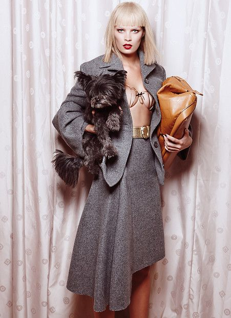 Franziska: graues Woll-Kostüm mit asymmetrischem Rock und Ärmel-Volants, goldener Gürtel, alles von Prada. Metall-BH von La Perla. Ledertasche von Longchamp