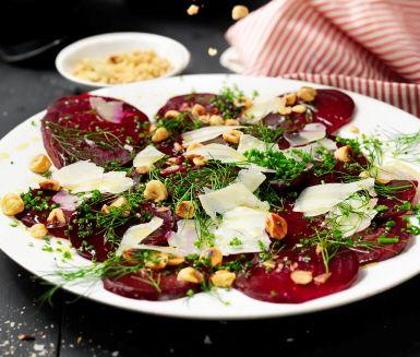 En enkel förrätt med tunt hyvlade rödbetor som toppas med grovhackade hasselnötter, lagrad ost och vit balsamico. Perfekt rätt att väcka smaklökarna med!