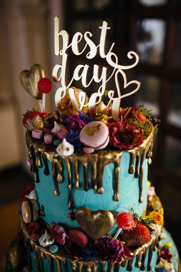 Blue and gold wedding cake decorated with fresh flowers, fruits and sweets. Images by Freckle Photography.