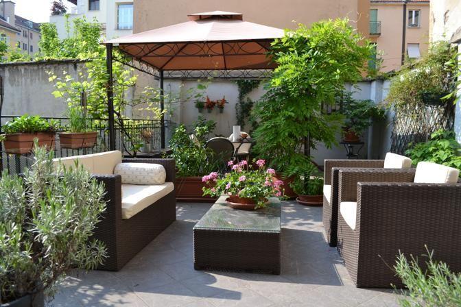 esta terraza es grande, tiene muchas plantas, tiene un banco (con una maceta) entre un sofà grande (a la izquierda) y 2 sillones (a la derecha), detràs del banco hay 3 macetas, detràs de las macetas hay un cenador  y  debajo del cenador hay una mesa con muchas sillas