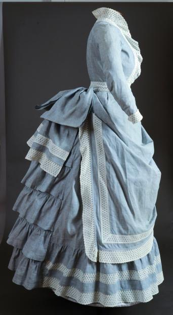 Robe pour le bord de mer, vers 1880, en toile de coton chinée bleu ciel, corsage cintré à basques rondes, garnitures de volants et entredeux en broderie anglaise. Jupe à tablier drapé à 5 hauteurs de volants sur la tournure, (usures et restaurations).