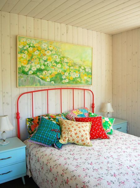 A beach house bedroom should have all of these elements; color, airy bedding, random art pieces and fun.