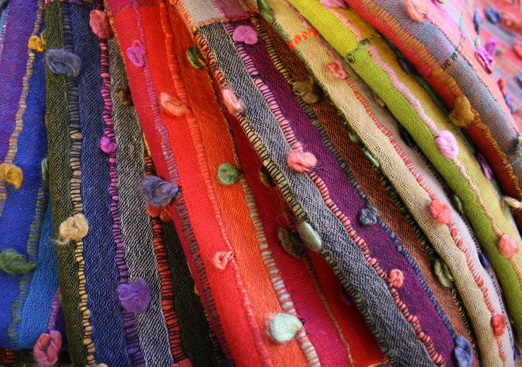 Colourful fine wool bobble scarves from India.