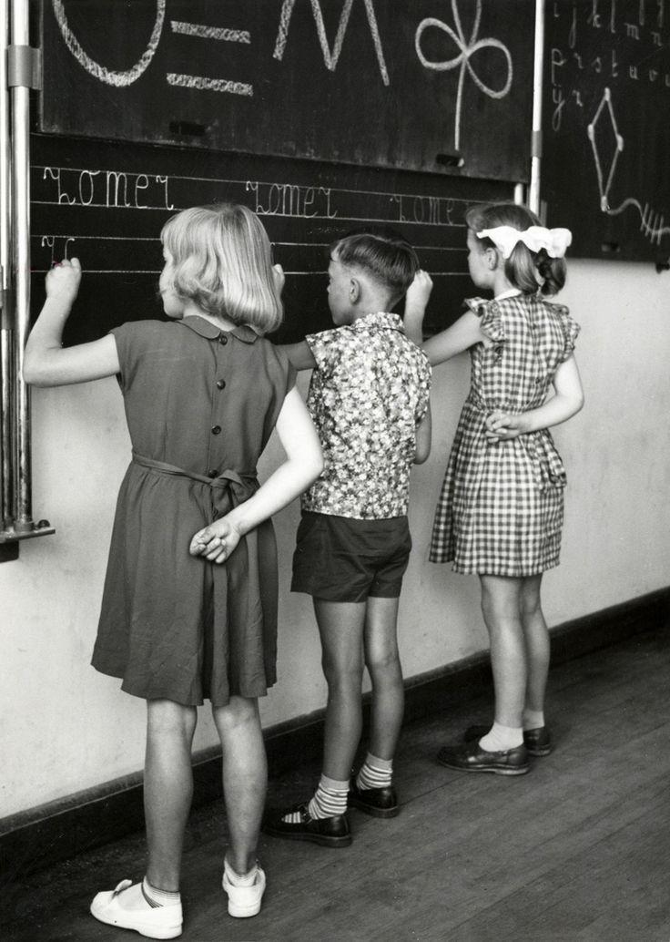 Schrijfles op de lagere school: Drie kinderen staan schoonschrijven te oefenen op een gelinieerd schoolbord in 1957.