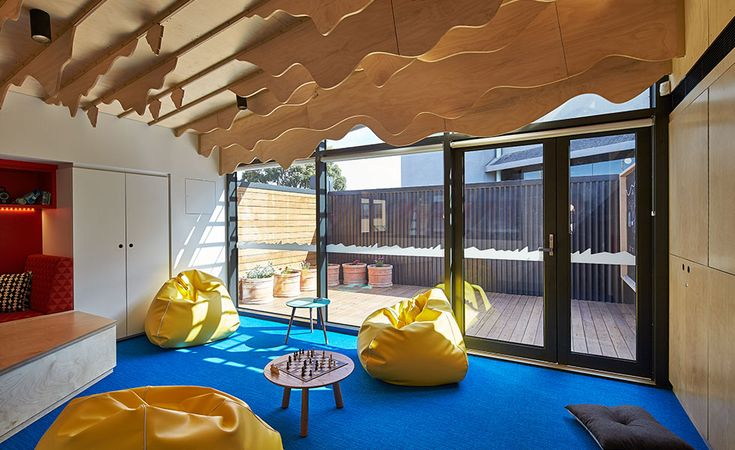 Playing cards in the Cubbyhouse at Broadmeadows Children's Court with yellow bean bags and plywood fins suspended above | Cubbyhouse by Mihaly Slocombe (2014-15) | Broadmeadows, Victoria, Australia | Photo: Peter Bennetts