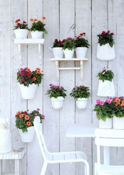 Ruimtegebrek in de tuin? Gebruik de schutting. Schilder die wit en maak een compositie van planken plantenpotten en -tassen.