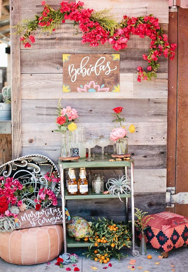 This Cinco de Mayo wedding inspiration is bursting with color. We love the way they used a bar cart to set up a margarita and beer station, flanked by fresh florals and a great display sign!