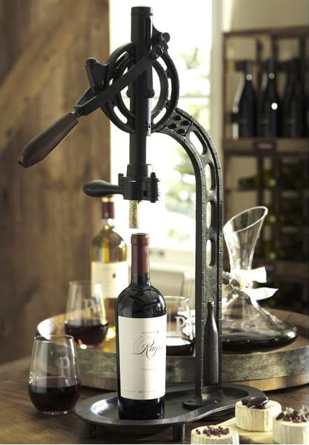 Modeled after a vintage professional wine opener, this tabletop version securely holds a wine bottle in place for uncorking.