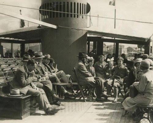 Passagiers zitten op het dek van een plezierboot in de zon, vlakbij de schoorsteen van het stoombootje. Rotterdam, rivier de Lek, Nederland, 1931.