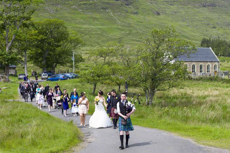 Traditional Scottish Wedding the piper leading the Bride and Groom from Clachan Church to the Wedding Reception in Applecross, Highlands of Scotland. This a remote part of the Scottish Highlands on the Road to the Isles.  Only get married in Summer as it would be impossible in Winter.  Photo: blog.corbin.com