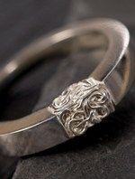 Strakke zilveren ring met een van zilverdraad gehaakt en geperst blokje ertussen.