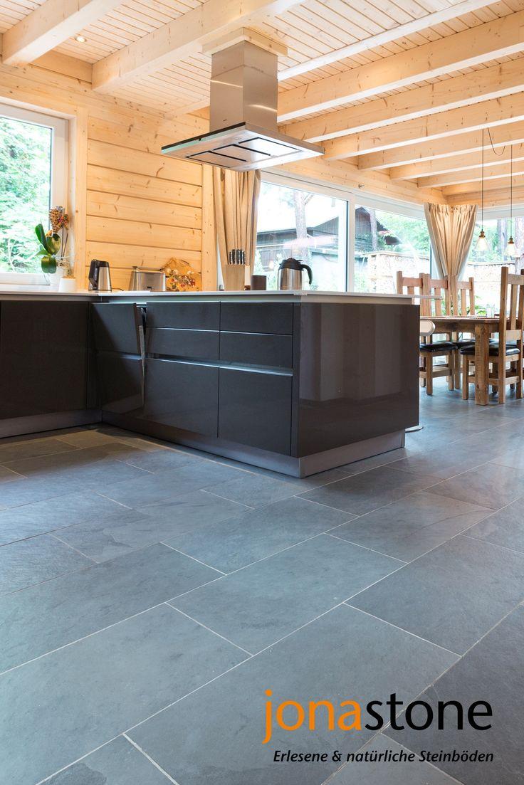 Besonderer Kontrast zum skandinavisches Holzhaus: ein eleganter grauer Schieferboden in Küche und offenem Wohn- und Esszimmer