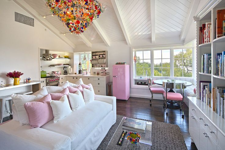 Fun one room apartment features vaulted herringbone paneled ceiling adorned with an eclectic multi-colored chandelier over a slipcovered white sofa lined with pink pillows across from a CB2 Peekaboo Clear Coffee Table and built-in bookcases alongside a chunky jute rug.