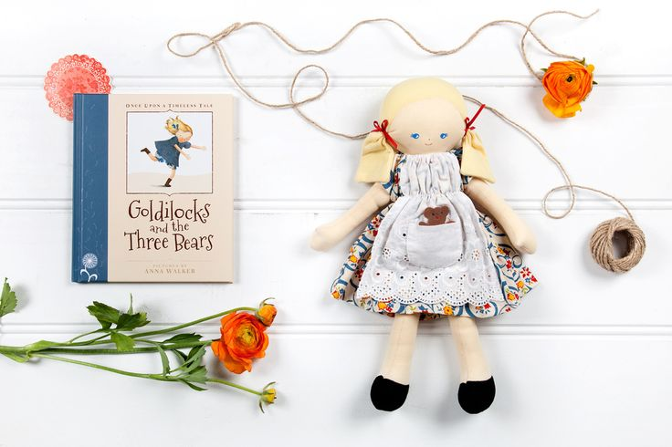 Golden Child: Goldilocks Doll by Alimrose Designs with cute little white broderie pinafore with little teddy in the pocket over gorgeous floral print dress along with little ribbons in her pigtails. 38cm tall (designed in Australia) Book Goldilocks and the Three Bears, a classic and beautifully illustrated by Anna Walker with story to read to little ones