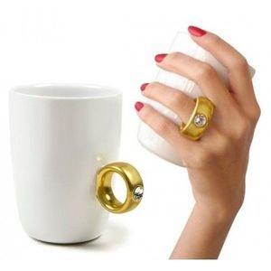 Você tem uma amiga que sonha em se casar? Que tal presenteá-la com uma caneca que já vem com um anel na alça? Feita de porcelana branca, o encaixe para o dedo imita um solitário com brilhante e o mais divertido: ela vem em uma caixa grande semelhante uma caixa de jóia, na qual, só o anel fica aparecendo, então quando a pessoa abre a caixa pela primeira vez, a reação é bem divertida! Ideal também para namorados e/ ou noivos que tenham fama de 'enrolados' e queiram presentear sua amada…
