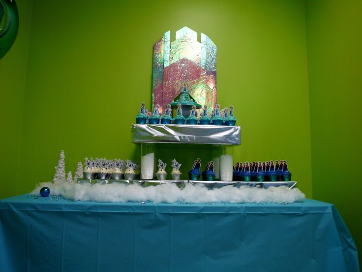 Cupcake table. Elsa castle credited to http://completelytypea.wordpress.com/2014/05/18/how-to-make-elsas-ice-castle-from-disneys-frozen. The castle was made from foam board, painted with acrylic paint and covered with iridescent flowerwrap. Stand was made from boxes covered with silver paper, pillars are dollarstore vases filled half way with polystyrene balls.