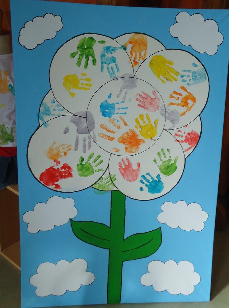 Schilderdoek met de handjes van de kindjes en de juffen. Ze hebben dit met verf afgedrukt op de vorm van een bloem.
