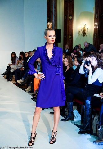 Violet Blue Satin Crepe wrap-over dress with side tie sash with ruffles around the neckline and sleeves.
