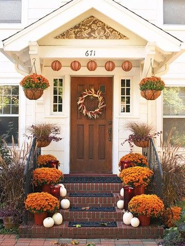 Several great things about this photo: pumpkin lanterns, window boxes with grasses, hanging mums, a fantastic wreath...and that stenciled triangle thing.