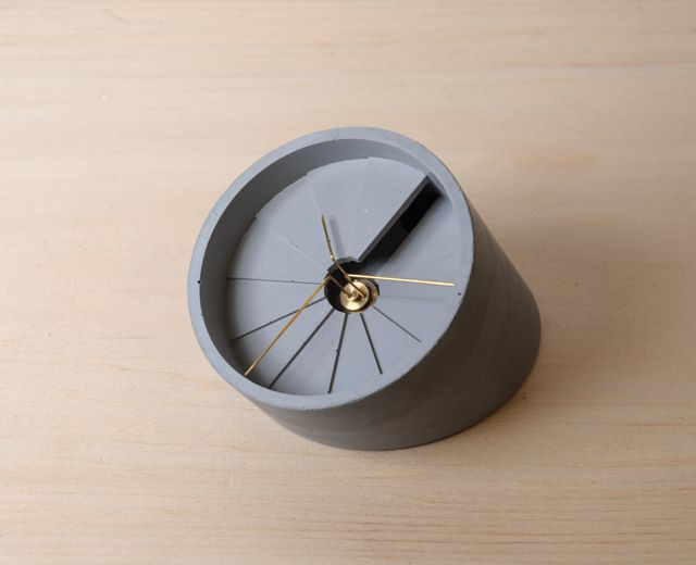 A tacle clock made of cement. The form of the clock is like a spiral staircase, and the hands are on its top level. Light and shadow changes with time in this clock. The concept of 4th Dimension Clock is to link time and space.