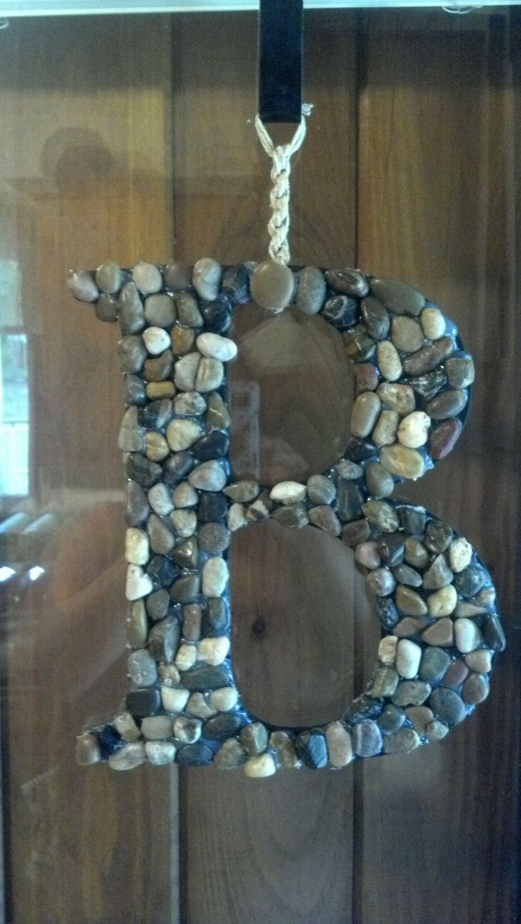 Wooden letter from craft store with river rocks from dollar store and some hemp to hang it by