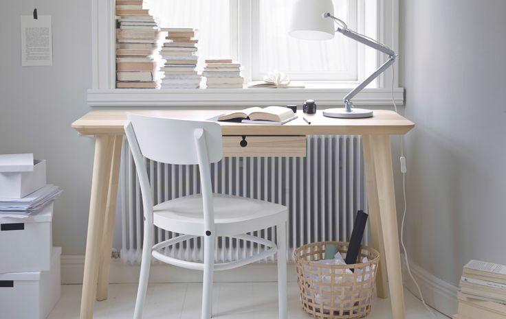 밝은 색상의 방안에 물푸레무늬목 책상과 화이트 의자가 있는 모습