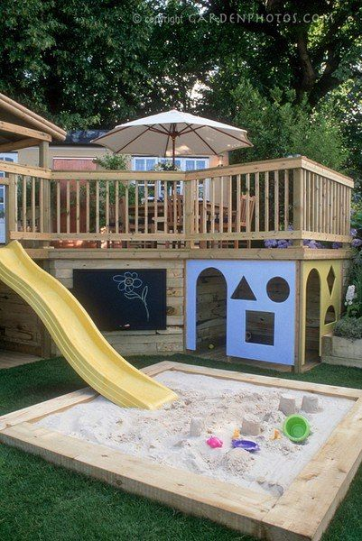 Playhouse built under deck with slide into sandbox. How awesome is that!?!?!? Great use of space!!!!