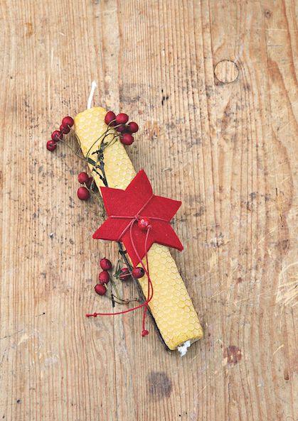 Ornez une #bougie en cire d'abeille d'une étoile en feutrine et de quelques #baies d'aubépine. Nouez le tout avec un fil de laine.   espritdici.com #feutrine #deco #noel #diy #couleur #laine #feutre #christmas