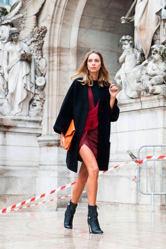 Impecable Puro estilo combinando vestido rojo sangre con abrigo 'oversize' en negro, bolso-cartera color naranja y botines verde petróleo.