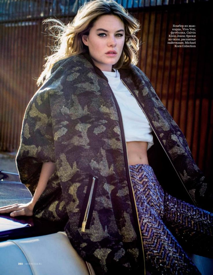 Model Camille Rowe layers up in oversized sweater, cropped top and sequined pants
