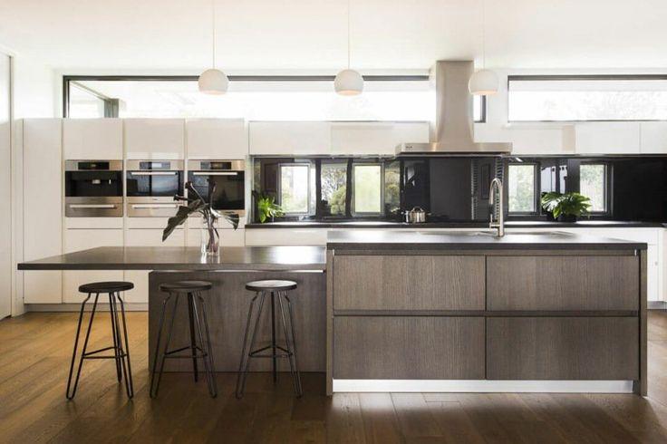 cuisine élégante avec îlot en bois et bar petit déjeuner, armoires blanches et suspensions demi-cercle
