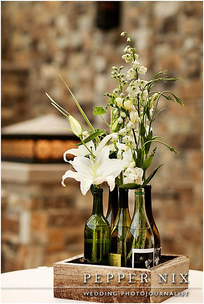 Centerpiece wooden box with custom wine bottles and simple white lilies with greenery.