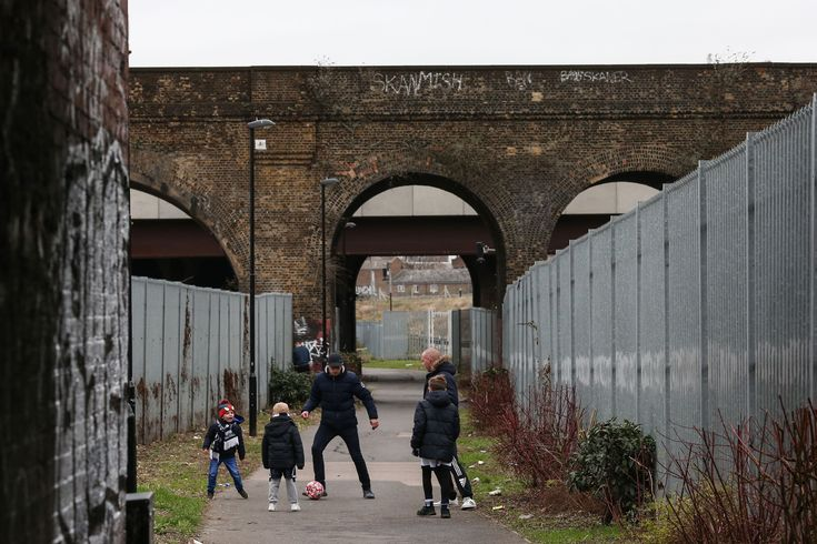 Three young boys and their dads play football beneath the arches of a railway bridge as they make their way to the match between Millwall and Rochdale at The Den. Millwall scored a 90th-minute equaliser to earn a replay Photograph: Charlotte Wilson/Offside via Getty Image