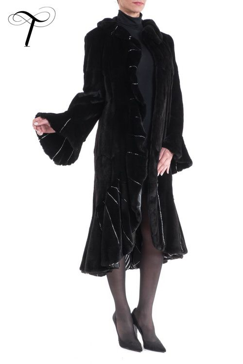Toutountzis Furs/BLACK SHEARED WEASEL FITTED COAT This astounding coat refines all aspects of one's #femininity. Crafted from soft black sheared weasel #fur, the coat emphasizes the figure with a line that is cinched at the waist and smoothly flares from the hips down. Featuring a ruffled collar, cuffs and right edge, it finishes with a lavish broad ruffled hem. Hand sawn strass chains accentuate the folds of the ruffles. A guarantee for an eye-catching appearance on special evening outings.