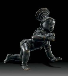 A bronze figure of Balakrishna  South India, Vijayanagar Period, 14th/15th Century  The baby Krishna depicted in a crawling position, wearing multiple chains around his waist, necklaces and other jewelry, his face surmounted by a multi-tiered flared headdress, holding a ball of butter in his right hand 5 1/8 in. (13 cm.) wide