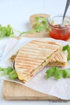 pita tosti met kip, chilisaus, oude kaas en halve avocado in plakjes