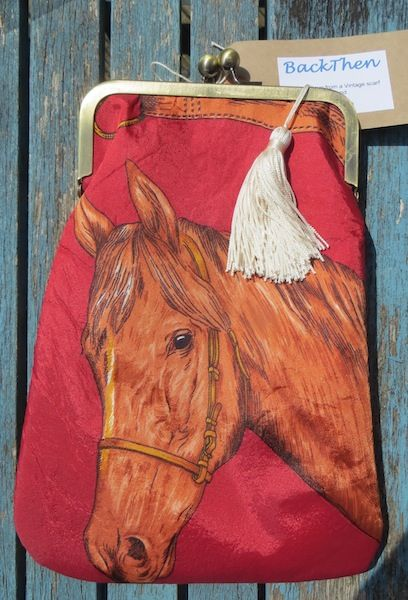 'Dobbin'.  A beautiful hand-painted 1960' scarf, with red background, has been used to great effect in this cross-body bag.The front features a horses head and the back shows stirrups, reins and horseshoe.  An ivory tassel completes the look