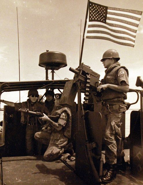 428-GX-USN 1135577_Box 875: Secretary of the Navy Paul R. Ignatius, (right), witnesses a demonstration of River Patrol Boat (PBR) weapons. Gunner's Mate Second Class Vincent Rincan, (left), mans the Mark 18 Rapid Fire Grenade Launcher while Lieutenant Commander Bob L. Peterson, Commander, Bassac River Patrol Group III, holds the M-79 single-shot grenade launcher, Republic of Vietnam, October 1968. Photographed from reference card.