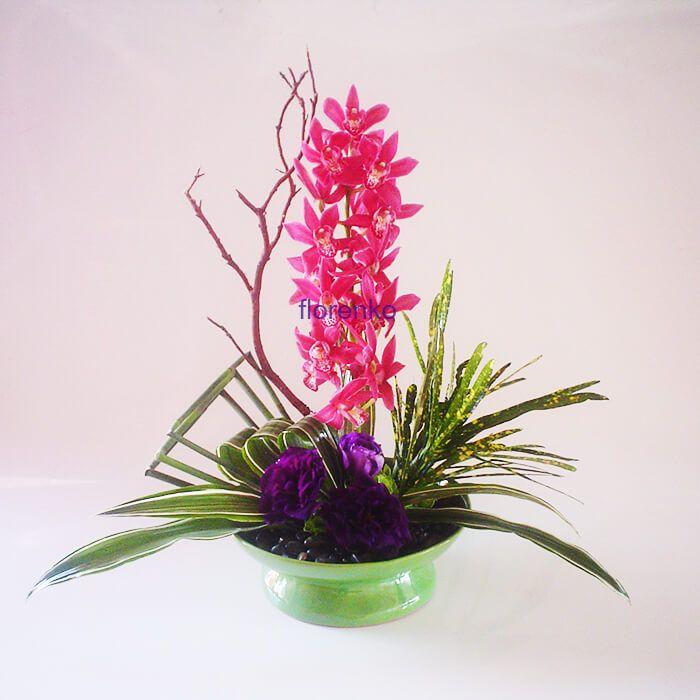 La magia de los colores en este fino diseño de orquídeas miniatura en rosadas tonalidades acompañadas de lisyantus azul intenso, piedra negra de rio, todo un delicatesen para aquellos que gustan de la contemplación.     Realizado con vara de orquídea miniatura con un mínimo de 12 flores (tono de las flores puede variar dependiendo de la temporada-tratamos de apegarnos a los colores lo mas posible), exóticos follajes, base cerámica verde brillante.