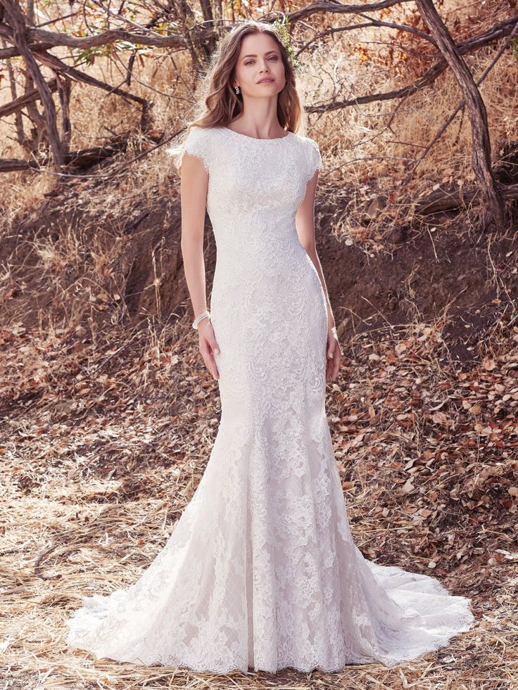 Maggie Sottero - HUDSON LYNETTE, Romantic lace appliqués cascade over crosshatched tulle and Inessa Jersey in this modest fit-and-flare wedding dress, featuring cap-sleeves and bateau neckline. Finished with covered buttons over zipper closure.