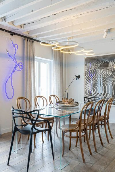 The dining room features a Glas Italia table that's paired with vintage Thonet chairs and two black Kartell chairs. The neon art is by Gun Gordillo and the piece on the right is by Alexandre Arrechea.