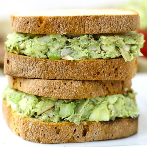 Two healthy tuna sandwiches stacked on each other made with avocado. and served on whole grain bread.