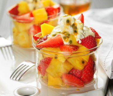 En exotisk fruktsallad med kryddig mango, söt ananas toppad med röda jordgubbar och honungsötad yoghurt smaksatt med passionsfrukt. Lär dig knepen hur du enkelt tärnar mango och ananas till den här hälsosamma fruktsalladen. Perfekt som frisk och fräsch efterrätt eller lyxigt mellanmål.