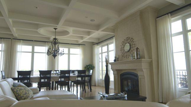 Dans cette demeure, les moulures en bois naturel encadrent les fenêtres qui offrent une vue sur un espace extérieur en pleine nature.