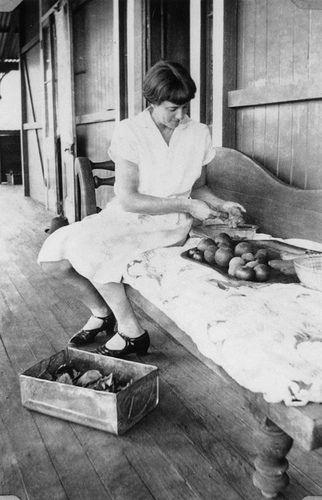 Young woman on the verandah preparing fruit for preserves, ca. 1930